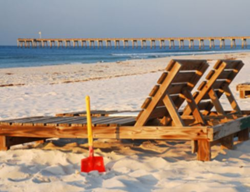 Florida shore with wooden lounge chairs on the beach